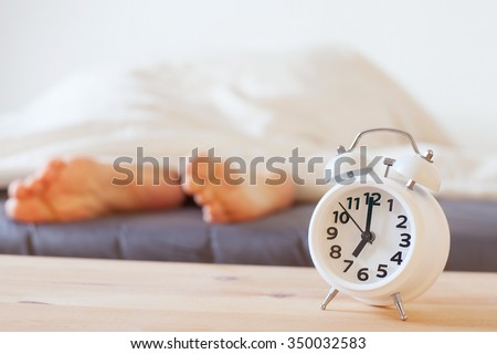 alarm clock and feet of sleeping person, morning concept, wake up - stock photo