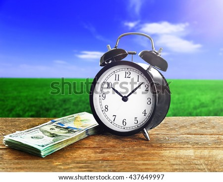Alarm clock and money on wooden table. - stock photo