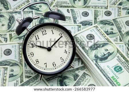 alarm clock and one hundred dollar bills - stock photo
