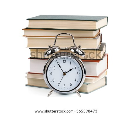Alarm clock and stack of books on a white background - stock photo