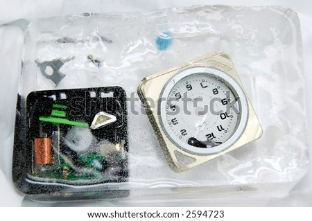 alarm clock breakout showing many plastic components  encapsulated in ice - stock photo
