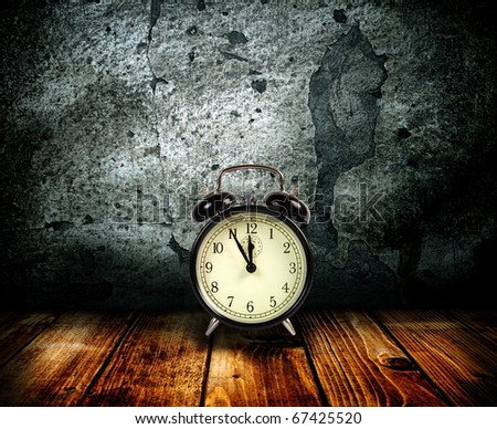 Alarm clock on a background of an old wall. - stock photo