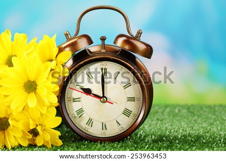 Alarm clock on green grass, on nature background - stock photo