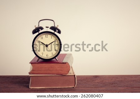 Alarm clock on old book on table. Vintage filter. - stock photo