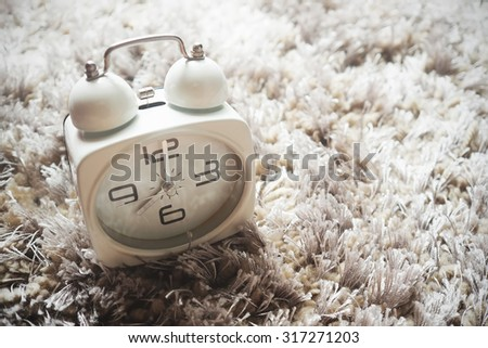 Alarm clock on soft fabric. Vintage effect. - stock photo