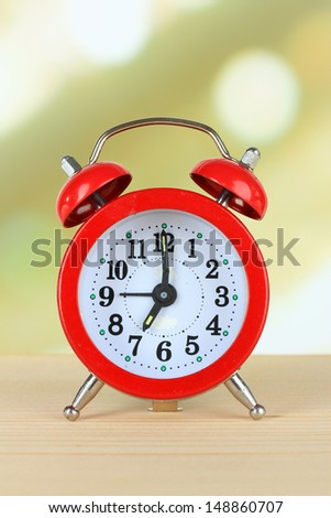 Alarm clock on table on light background - stock photo