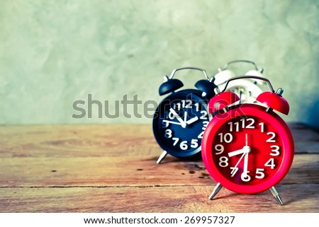 alarm clock on wood table in vintage color style - stock photo