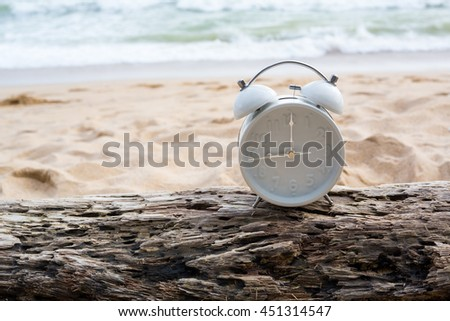 alarm clock on wood timber, sand background - stock photo