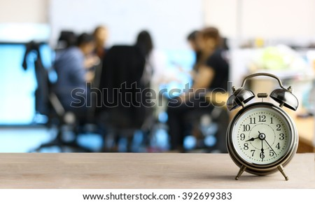 Alarm clock on wood with blurred abstract background of business discussion people group or  meeting team,time concept at early morning or Overtime in evening - stock photo