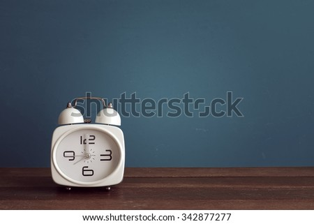 Alarm clock on wooden table front blue background. Vintage effect. - stock photo