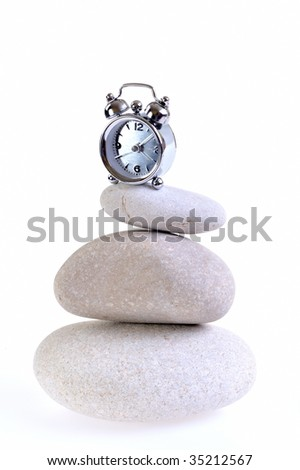 alarm clock over stones against white background - stock photo