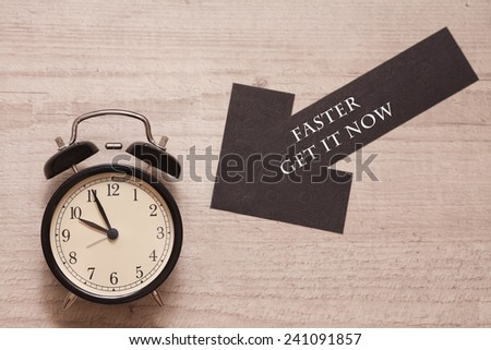 alarm clock showing almost ten with arrow sign indicating to be faster and get it now - stock photo