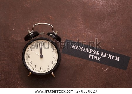 alarm clock showing almost twelve o'clock and indicating to have business lunch - stock photo