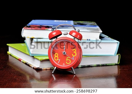 alarm clock showing 12 o'clock with a book on the wooden table - stock photo