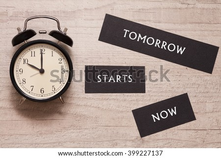 alarm clock showing ten o'clock and indicating that tomorrow starts now - stock photo
