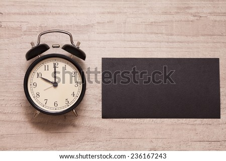 alarm clock showing ten o'clock with blank sign on the wooden background - stock photo