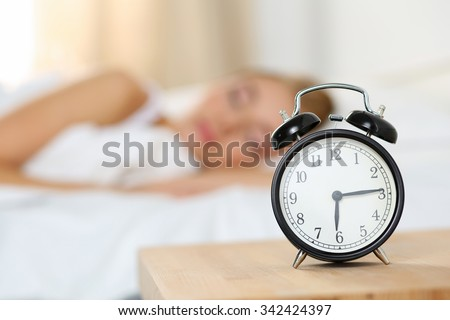 Alarm clock standing on bedside table going to ring early morning to wake up woman in bed sleeping in background. Early awakening, not getting enough sleep, oversleep, getting work time concept - stock photo
