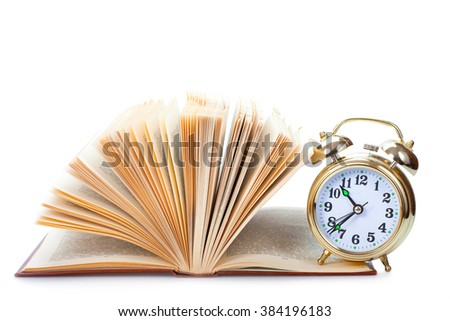 alarm clock to stand on the open book - stock photo