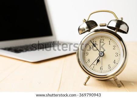 Alarm clock with computer laptop on desk - stock photo