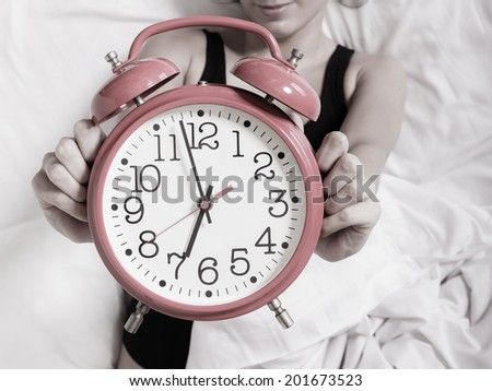 Alarm clock with female hands. Sexy woman lazy girl lying on bed and showing the time. - stock photo