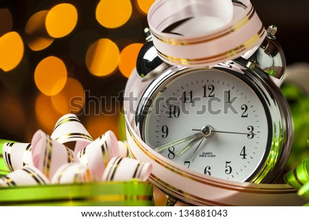 Alarm clock with ribbons against unfocused background - stock photo