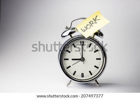 Alarm clock with sticky paper note WORK time on white background - stock photo