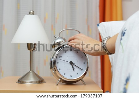 Alarm clock with woman  in bed - stock photo