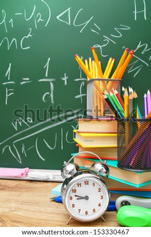 Alarm clocks and school accessories against a school board (the formula on on the physicist). - stock photo