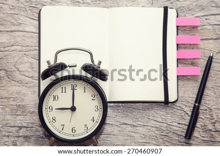 alarm showing nine with notepad and pen on the background. close up, selective focus - stock photo