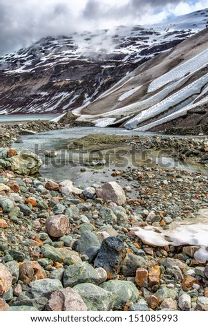 Alaska Glacier Bay National Park landscape with tumbled rocks and a stream of water in the foreground against a backdrop of glacial ice. Concept for climate change. - stock photo