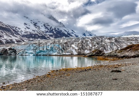 Alaska glacier landscape with reflections in a blue lake of melted glacial water. Location: Reid Glacier at Glacier Bay National Park - stock photo