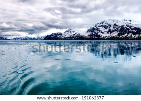 Alaska wilderness landscape at Glacier Bay National Park, featuring floating ice, dramatic clouds and snowy mountains with reflections in the bay's blue water. - stock photo