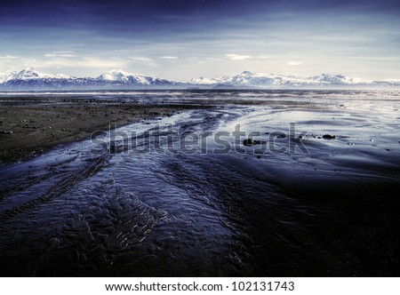 Alaskan beach near Homer at low tide with water flowing to the sea and snow covered mountains in the background. - stock photo