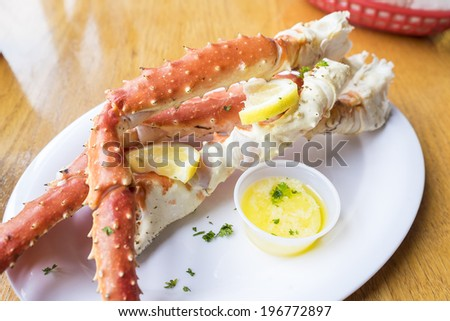 Alaskan King Crab Legs Served with Butter and Lemon Slices - stock photo