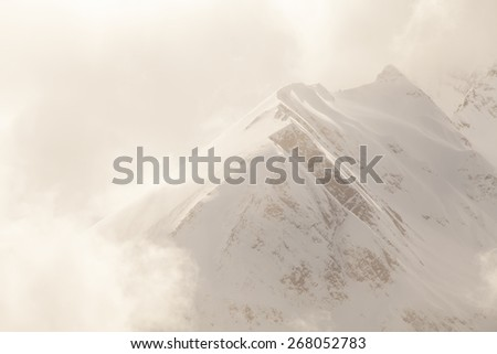 Alaskan mountain ridge in winter with snow in fog and low clouds. - stock photo