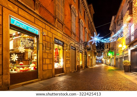 ALBA, ITALY - DECEMBER 07, 2011: Pedestrian street and shops in old town illuminated for Christmas celebrations. This area is very popular with locals and tourists visiting Alba for winter holidays. - stock photo