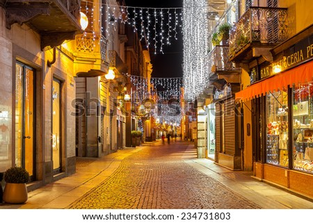 ALBA, ITALY - DECEMBER 06, 2012: Pedestrian street in old town illuminated and decorated for Christmas and New Year holidays. This area is very popular with locals and tourists visiting Alba. - stock photo