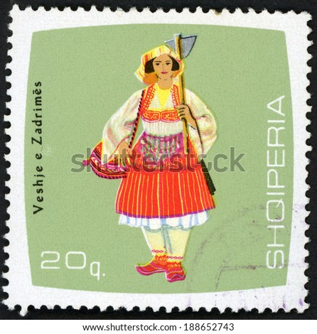 ALBANIA - CIRCA 1967: post stamp printed in Albania (shqiperia) shows farmer woman holding hoe from Zadrimes; regional costumes series, Scott 1052 A227 20q green red yellow, circa 1967 - stock photo