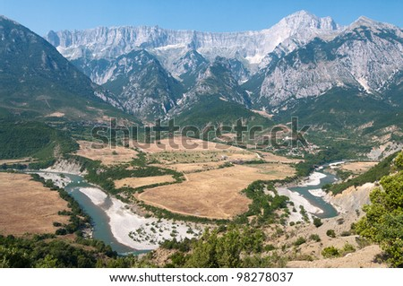 Albania: landscape of a cultivated plateau between a bend in the Vjosa river and the mountains in the Permet district - stock photo