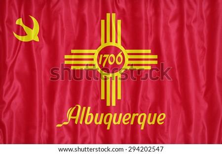 Albuquerque ,New Mexico flag pattern on fabric texture,retro vintage style - stock photo