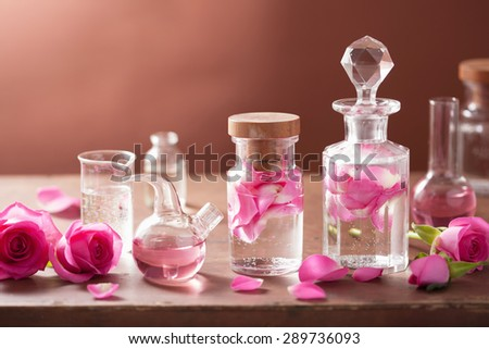alchemy and aromatherapy set with rose flowers and flasks - stock photo