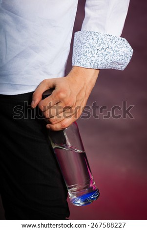 Alcohol addiction concept man holding in hand vodka bottle - stock photo