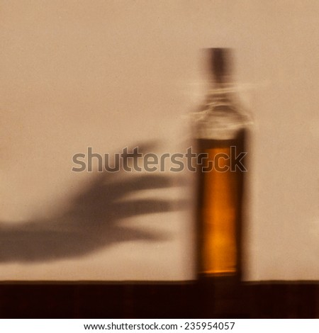 Alcohol addiction concept - shadow of hand reaching for bottle of alcohol - stock photo