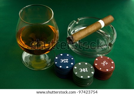 alcohol, chips and cigar on a green background - stock photo