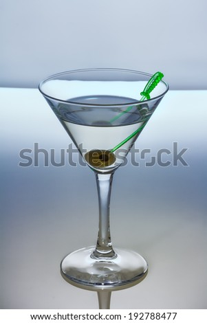 Alcohol cocktail with dry martini and olive on skewer - stock photo