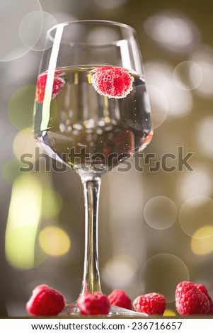 Alcohol cocktail with raspberry on the yellow blurred background - stock photo