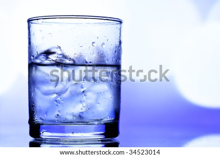 Alcohol drink with ice over blue background - stock photo