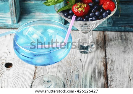 Alcohol in stylish blue color glass glass on long stalk - stock photo