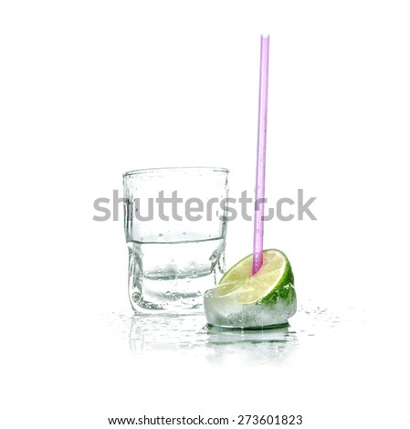 Alcohol - vodka drink with ice, lime and drinking straw over white background - stock photo