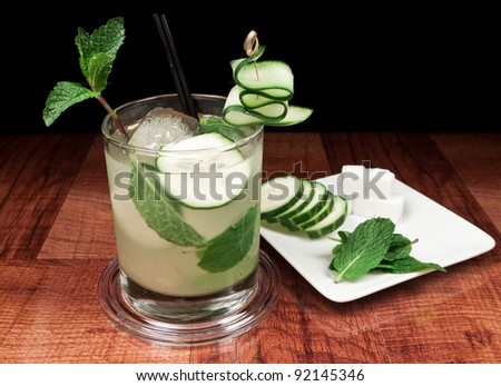 alcoholic beverage on a bar top with cucumber slices, mint and sugar cubes on a plate - stock photo